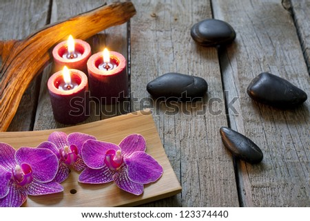 Orchid on wooden boards with stones spa cosmetic abstract vintage concept with candles