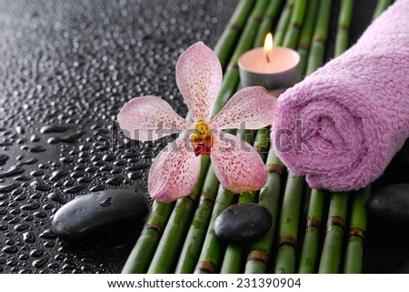 orchid with black stones ,candle ,towel on bamboo grove on wet background - stock photo