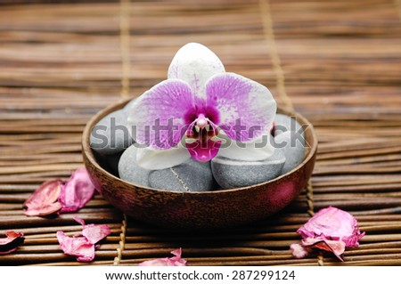 orchid with gray stones in wooden bowl with petals on mat  - stock photo
