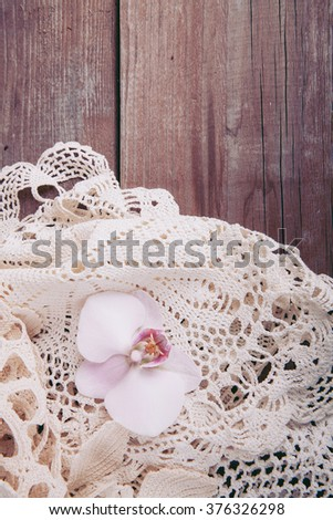 orchids and lace on the wooden background