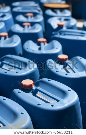 Ordered old blue canisters for oil products. - stock photo