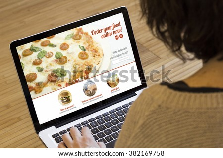ordering food online concept: woman with a laptop showing fast food website on screen. Screen graphics are made up. - stock photo