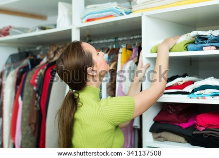 Orderly brunette housewife arranging clothes at wardrobe indoor - stock photo