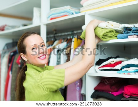 Orderly happy woman arranging clothes at wardrobe indoor - stock photo