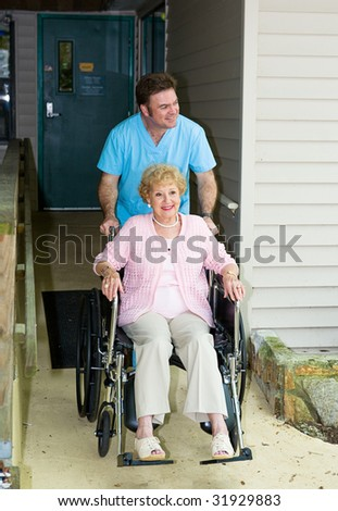 Orderly takes a disabled senior woman out for a walk.