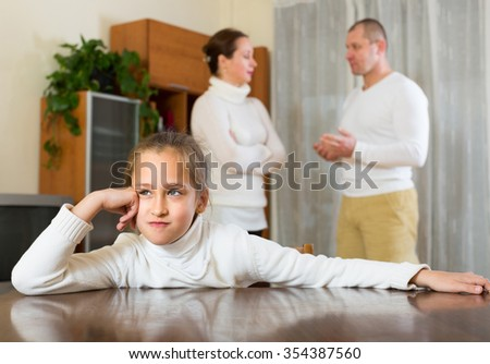 Ordinary adult couple with preschooler daughter having conflict at home. Focus on girl - stock photo