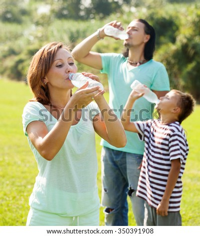 ordinary adult couple with teenager drinking water from plastic bottles in summer