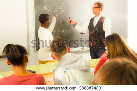 ordinary Aframerican student boy answers near blackboard at math lesson