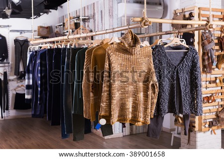 Ordinary apparel store with different clothes on hangers - stock photo