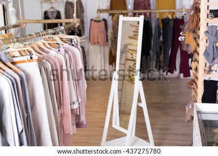 Ordinary apparel store with knitted fabric clothes on hangers - stock photo