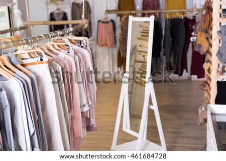 Ordinary apparel store with knitted fabric clothes on hangers