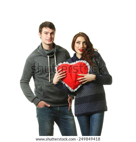 Ordinary beautiful couple having fun with a pillow in the form of heart on Valentine's Day. On a white background.