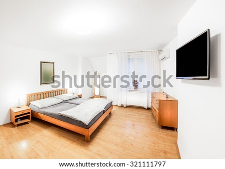 Ordinary bedroom of the house in wooden style with double bed, bedside tables, mirror, chest of drawers and a modern TV. Bedroom is lit by bright light mounted on the ceiling and two bedside lamps.