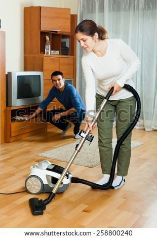 Ordinary couple doing housework together in home - stock photo