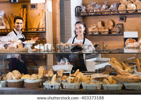 Ordinary couple selling fresh pastry and loaves in bread section - stock photo