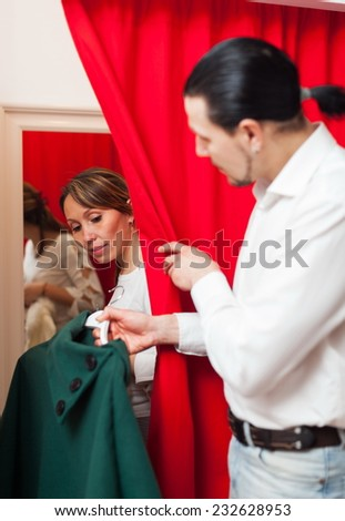Ordinary couple trying coat in fitting-room at clothing store