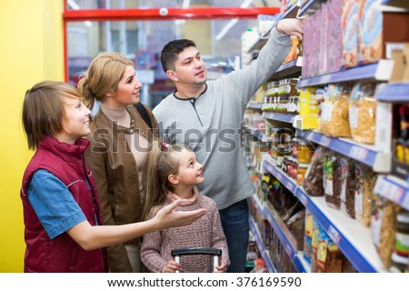Ordinary family of four buying cereal for breakfast in supermarket. Selective focus