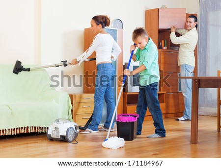 Ordinary family of three with teenager doing housework with  cleaning equipment in living room