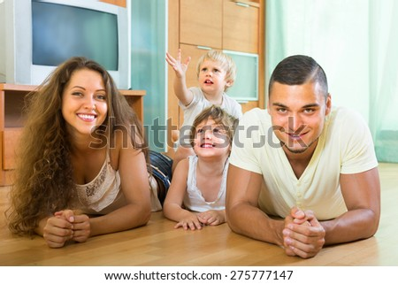 Ordinary happy family of four enjoying time in living room at their home. Focus on girl