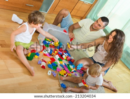 Ordinary happy family of four relaxing at home with toys