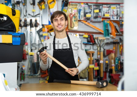 Ordinary male seller posing at tooling section of household shop