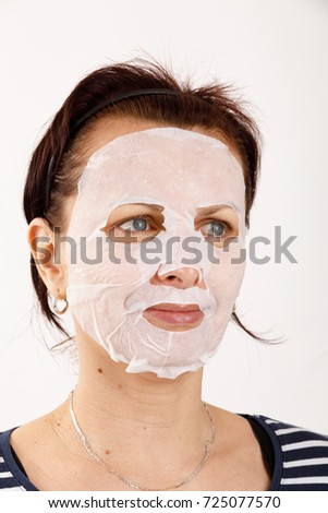ordinary middle-aged housewife woman with cosmetic sheet mask on her face