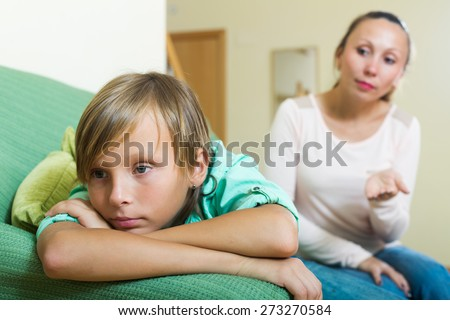 ordinary mother berating teenager son in living room at home. Focus on boy - stock photo
