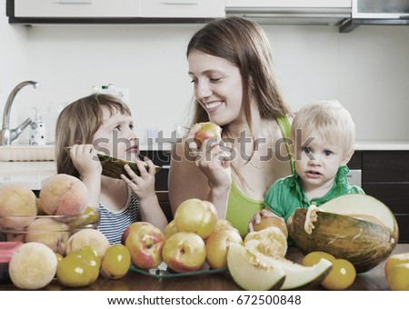 Ordinary mother with children eating melon and other fruits over  table at home interior