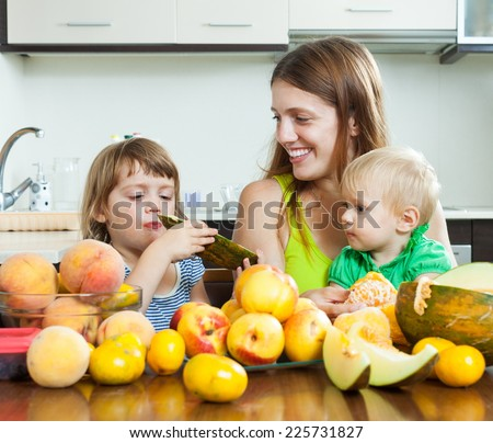 Ordinary mother with children eating melon and peaches over table at home interior