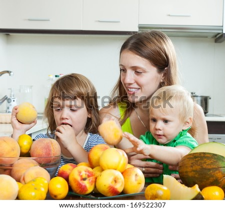 Ordinary mother with children together with melon and peaches over dining table