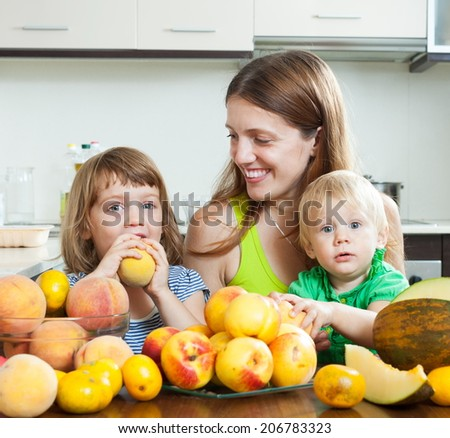 Ordinary mother with children together with melon and peaches over dining table at home interior