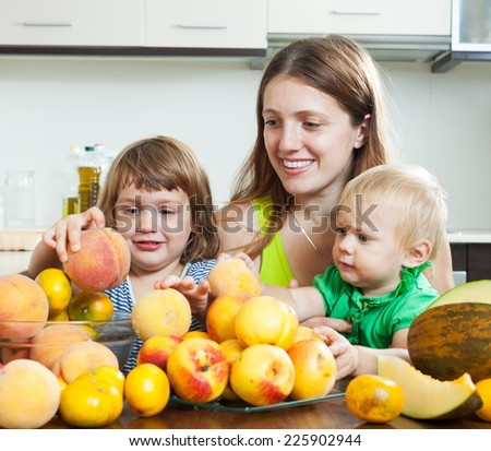 Ordinary mother with daughters together with melon and peaches over dining table