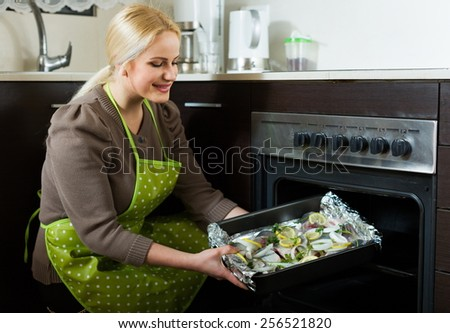 Ordinary woman cooking fish  in oven at home kitchen
