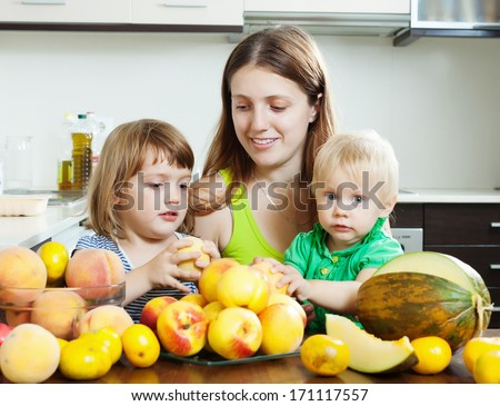 Ordinary woman with two daughters eating melon and peaches
