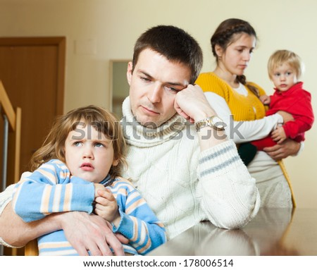 Ordinary young  family of four after quarrel in home - stock photo