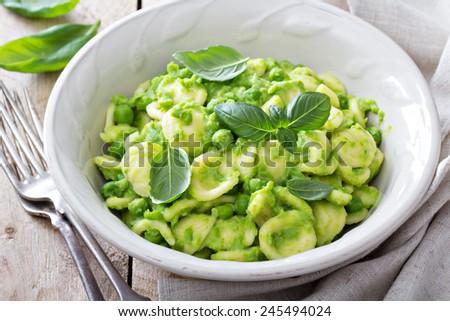 Orecchiette pasta with peas and fresh basil - stock photo