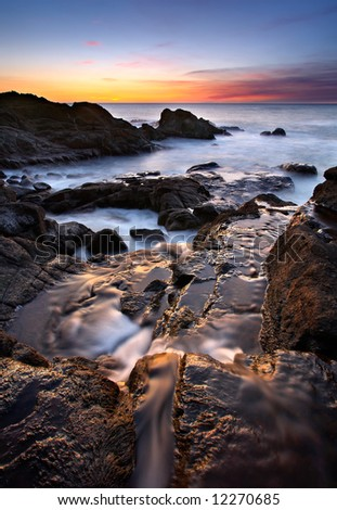 Oregon coastal scene, including a stream, the ocean, and sunset. - stock photo