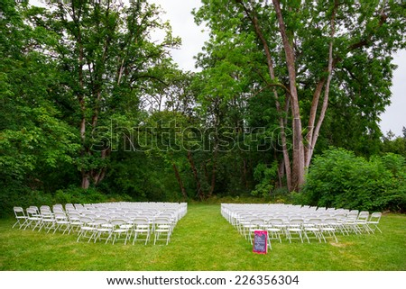 Oregon wedding outdoors with white chairs for seating in a meadow with green grass. - stock photo