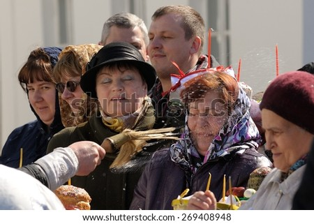 Orel, Russia, April 11, 2015: Traditional orthodox paschal ritual - priest blessing people with holy water in Iverskaya church, Orel, Russia horizontal - stock photo