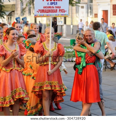 Orel, Russia, August 4, 2015: Orlovskaya Mozaika folk festival, young girls in pink dress and women hugging