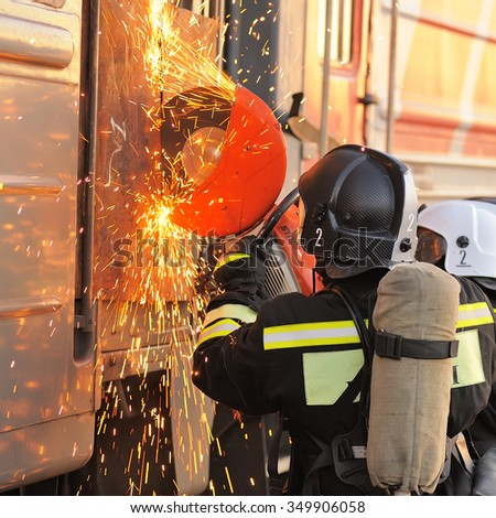 Orel, Russia - December 09, 2015: Emergency Control Ministry (MCHS) tactical exercise. Russian rescue team cutting carriage door with circular saw - stock photo