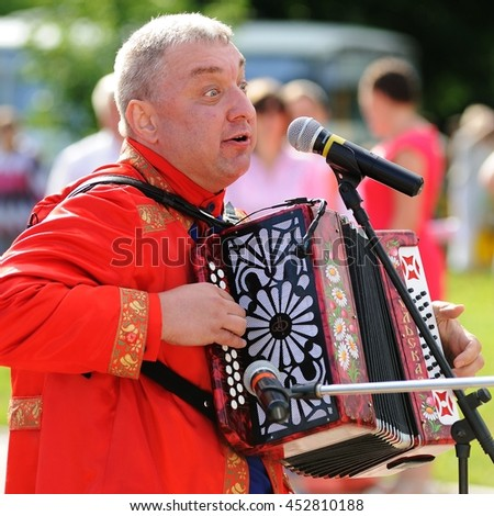 Orel, Russia - July 08, 2016: Russian Valentine Day  - Petr and Fevronia. Senior man in red outfit playing garmoshka, Russian accordion