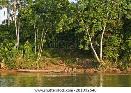 ORELLANA, ECUADOR - AUGUST 11, 2012: Unidentified local indigenous people next to the Napo river in the rainforest, Yasuni National Park. - stock photo