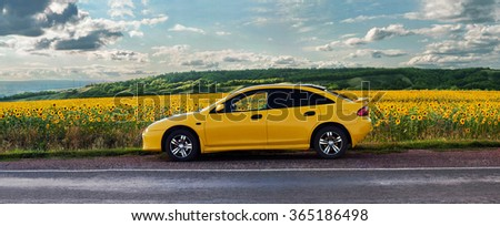 Orenburg, Russia-July 2015: Yellow car Mazda on the road along the sunflower field