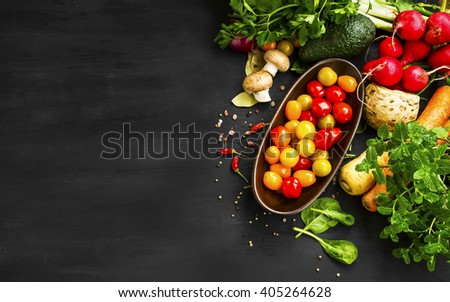 Organic and bio vegetables with tomatoes, radish, avocado, spinach , carrots, mushrooms and spices assortment on black wooden background - stock photo