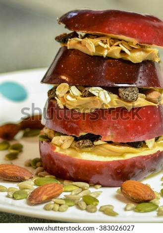 Organic Apple Sandwich with peanut butter, almonds, pumpkins seeds and oats, raisins  a  nutritional snack or meal for the health conscious person.