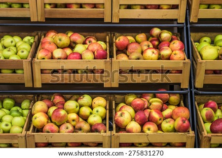 Organic apples in wooden boxes in the supermarket are sorted by varieties - stock photo