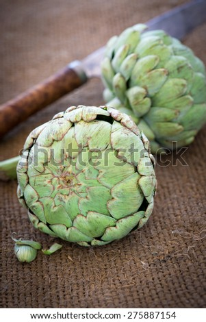 Organic Artichokes on burlap with a knife in the background - stock photo