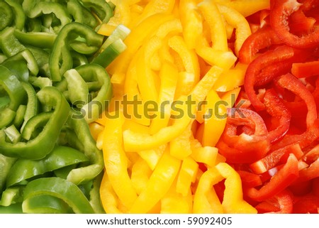 Organic background made of slices of green, yellow and red bell pepper. Organic flag of Mali. - stock photo