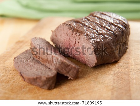 Organic Beef Sirloin Roast Sliced on Cutting Board - stock photo